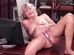 Nude granny on a desk drains her vag